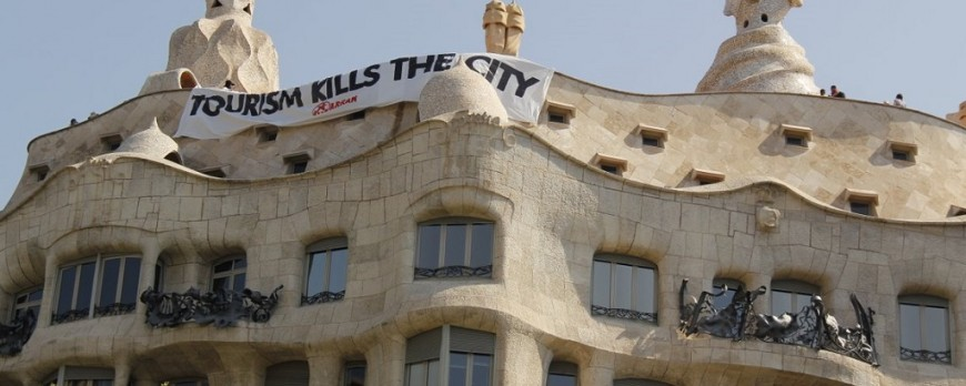 Arran hangs a banner in La Pedrera to protest against mass tourism